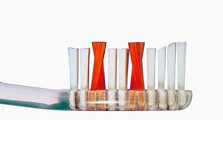 На фотографии показан пример зубной щетки с пучками щетинок разной длины и икс-образным их расположением